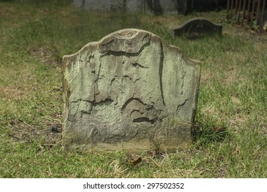 Half buried ancient weathered and flaking gravestone