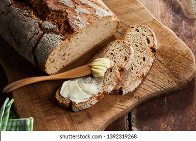 Half buttered slice of rye bread with spreader or butter knife on a wooden cutting board with crusty loaf viewed top down in close up