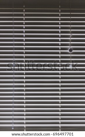 Half closed Venetian blinds hanging over a window