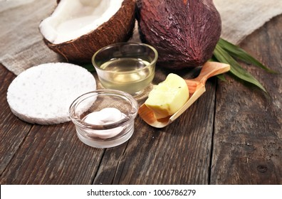 Half coconut with bottle of coconut oil, cosmetic cream, butter in wooden scoop, sponge and cocoa pod on wooden background.