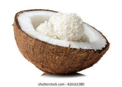 half coconut with coconut candies on white isolated background