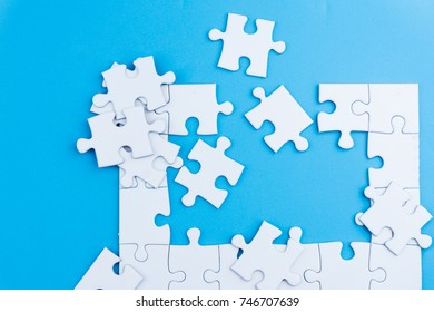 half complete white color puzzle on blue background. Task for completion concept. selective focus