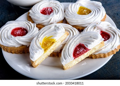 Half cookies covered with meringue and marmalade on a plate