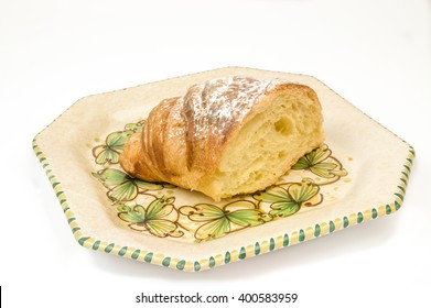 Half croissant in a dish on the table on white background