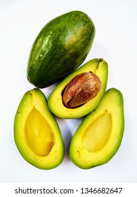 Half cut avocado, pellets and avocado meat on a white background
