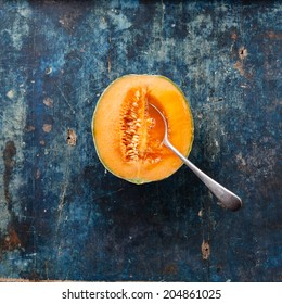 Half cut of ripe cantaloupe melon with spoon on blue background