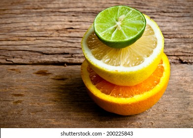 Half Cut Sliced Group of Citrus fruits Fresh Lemon, Green Lime and Orange on Wood Table Background, Rustic Still Life Style.