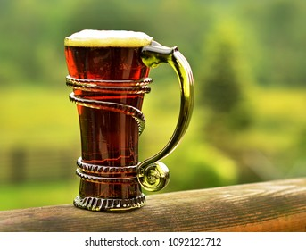 half dark beer in a vintage green glass on a wooden railing, green background