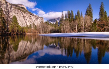 Half dome shrouded in clouds. The entire scene crisply reflected in the Merced River in Yosemite Valley.