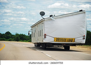 Half of double wide modular home being transported along interstate highway.