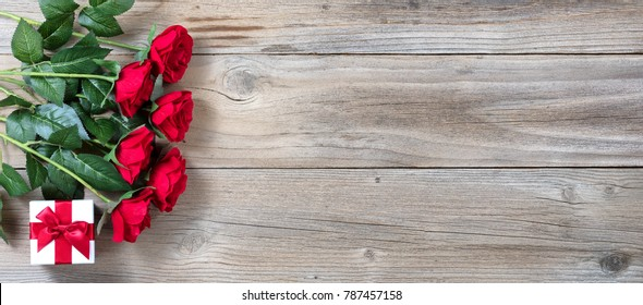 Half dozen red roses and gift box on left hand side of rustic wood in flat lay view