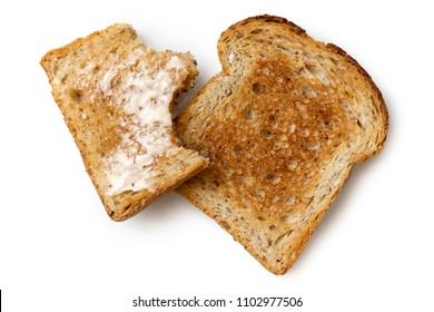 Half eaten buttered slice of whole wheat toast and whole dry slice of toast isolated on white from above.