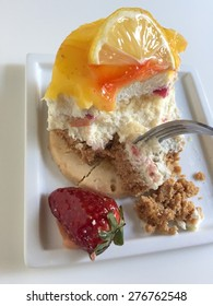 half eaten cheese cake decorated with strawberry and lemon