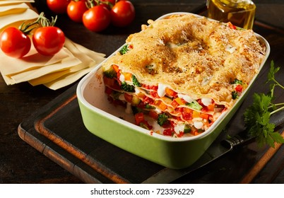 Half eaten dish of healthy fresh vegetable lasagne layered with pasta and mozzarella cheese served on a wooden board with fresh tomatoes alongside