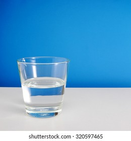 Half empty or half full glass of water on white table on blue background. (#1)