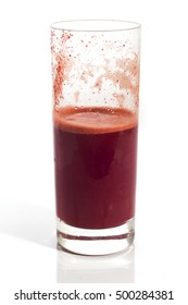 Half empty glass of healthy red juice over white background