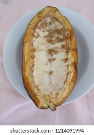 Half empty shell of cocoa on white plate, top view