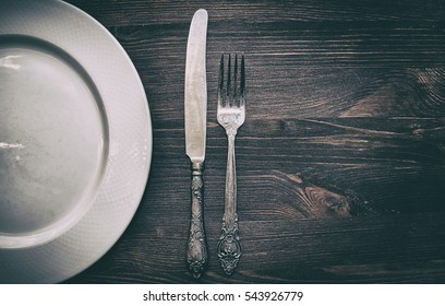 Half empty white plates, vintage knife and fork on brown table, above from view, vintage toning