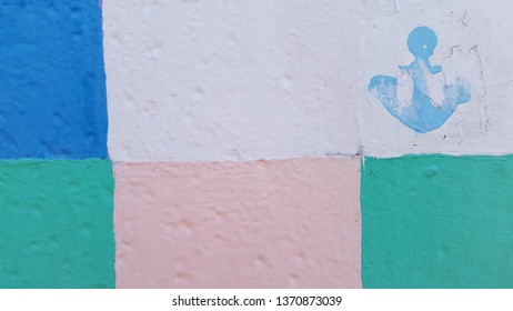 Half erased stamped anchor silhouette on uneven chopped surface of checkered painted background. Colorful grunge backdrop nautical style. Light blue marine symbol stamped on old painted metal gates