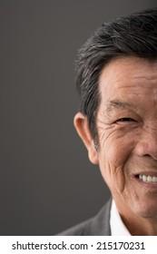 Half face close up portrait of senior Vietnamese man