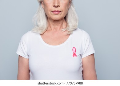 Half face cropped portrait of woman in white t-shirt with breast cancer pink ribbon and serious expression over grey background