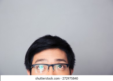 Half face portrait of asian man in glasses looking up at copyspace over gray background