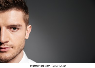 Half face portrait of a handsome confident man looking at camera isolated over grey background