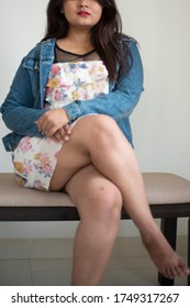 Half face portrait of an Indian Bengali beautiful and cute brunette girl in a casual blue jeans shirt and white top is sitting on a bench inside a room. Indian lifestyle and fashion portrait