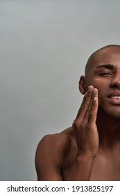 Half face portrait of shirtless young african american man applying lotion on his face, posing isolated over gray background. Skincare routine concept. Front view. Vertical shot
