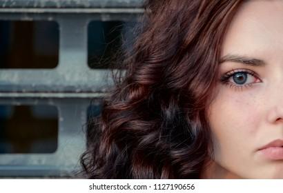 Half of face of sad depressed girl in front of metal grid, teenager prisoner or abuse victim concept