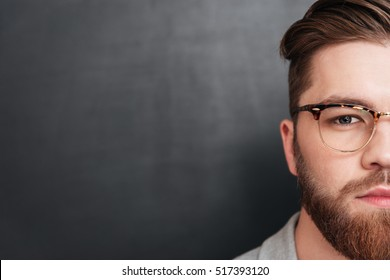 Half face of serious bearded man in glasses