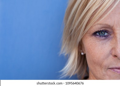 Half a face of a serious looking, middle aged, blond, Swedish woman against a blue background.