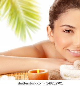 Half face of sexy brunette girl enjoying day spa on massage table outdoors, exotic beach resort, palm trees, well being and pleasure concept