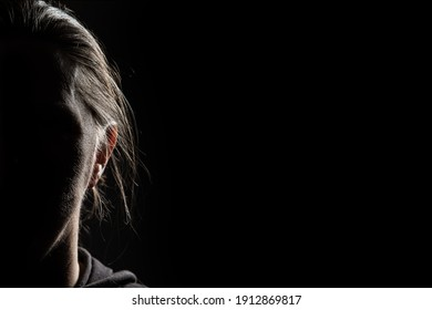 Half face of unrecognizable woman in shadow shrouded in darkness isolated on black background with wide copy space, concept of anonymity to hide one's identity, women who have suffered violence