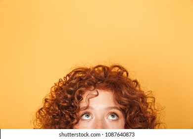 Half face of young curly redhead woman looking up at copy space isolated over yellow background