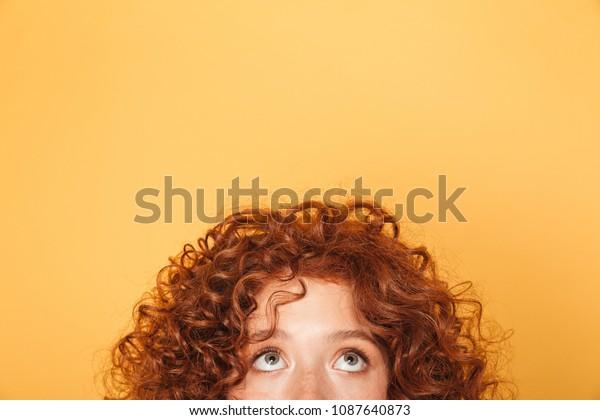 metade rosto de jovem encaracolado ruiva mulher procura até no cópia espaço isolado mais amarelo fundo
