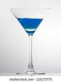 A half filled martini glass over white