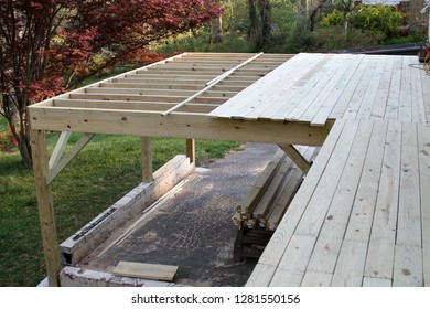 The half finished construction of a wooden outdoor deck in springtime with the framing done and boards nailed down across half of it