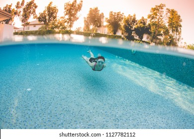 Half frame underwater picture of swiming woman in the pool.