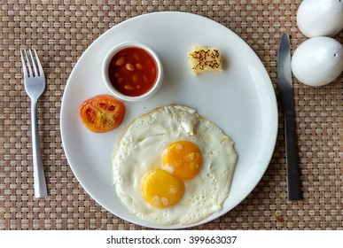 Half Fried Eggs with chutney and tomato slice, served on white plate and photographed against mat
