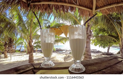 Half full glasses of tropical pina colada cocktail drink with pineapple garnish in glass with straws at exotic beach with thatched roof at Lefaga, Upolu Island, Western Samoa, South Pacific