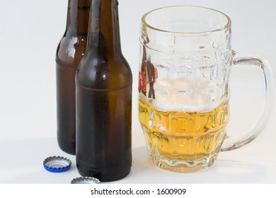 Half full pint glass and two bottles against a white background