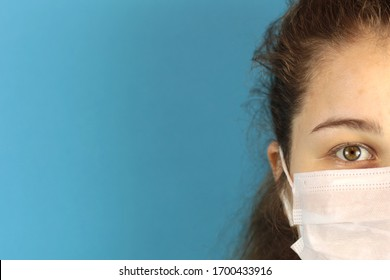 Half of the girl's face is a doctor in a protective mask. The fight against viruses. Personal hygiene. Blue background