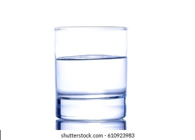 Half a glass of blue water on a white background