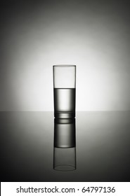 half glass of water on a reflexion
