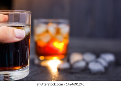 half a glass of whiskey and a cola with ice in the foreground in hand on the background of a glass with a drink out of focus