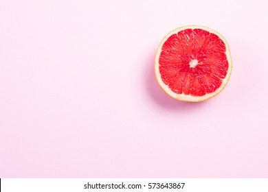 Half grapefruit citrus fruit on pink background