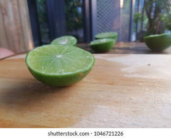 A half of green lemon on the wood background. Lemon is a vegetable with high vitamins, which contribute to health.