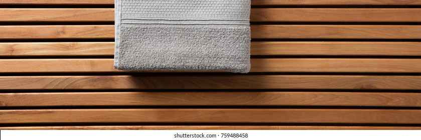 Half grey towel for spa, hammam, sauna, shower, bath, hygiene or body care concept with grey cotton towel set over beautiful wooden board, copy space long banner