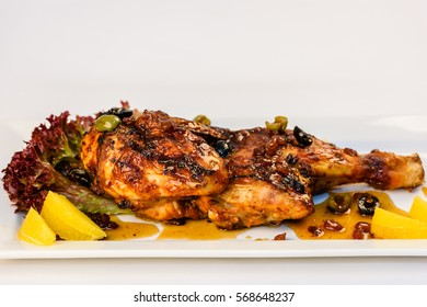 Half grilled chicken with greens on a white background